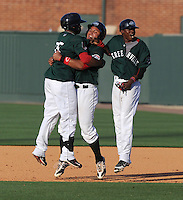 Left fielder Keury De la Cruz (25), left, of the Greenville Drive, celebrates his walk-off single with teammates Boss Moanaroa (29), center, and Jose Vinicio (36). De la Cruz's hit in the bottom of the 10th inning with the bases loaded gave the Drive a 6-5 win over the West Virginia Power in a game on May 20, 2012, at Fluor Field at the West End in Greenville, South Carolina. Greenville won 6-5. (Tom Priddy/Four Seam Images)