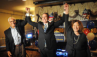 From left, John Cordisco, Steve Santarsiero and his wife Ronni Fuchs raise their arms after Santarsiero won the democratic nomination in the 8th district senate race at Temperance House April 26, 2016 in Newtown, Pennsylvania.  (Photo by William Thomas Cain)