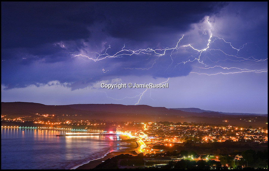 BNPS.co.uk (01202 558833)<br /> Pic: JamieRussell/BNPS<br /> <br /> ***Please Use Full Byline***<br /> <br /> A lightning storm over Sandown Bay.<br /> <br /> Stunning photographs have revealed a turbulent side to the normally genteel Isle of Wight.<br /> <br /> The seemingly benign south coast holiday destination has been catalogued over a stormy year by local photographer Jamie Russell, and his astonishing pictures reveal the dramatic changes in weather that roll across the UK in just 12 months.<br /> <br /> Lightning storms, ice, floods, gales and blizzards have all been captured by the intrepid photographer who frequently got up in the middle of the night to capture the climatic chaos.<br /> <br /> Looking at these pictures prospective holidaymakers could be forgiven for thinking twice about a gentle staycation on the south coast island.