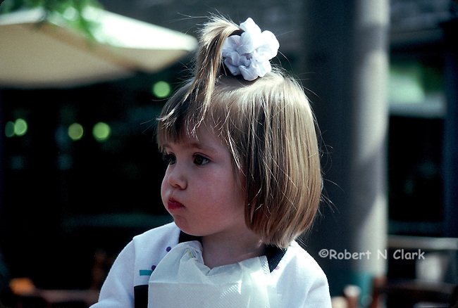 Young girl with ribbon on top of her hair and puffy cheeks