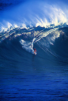 A surfer tow surfing at Jaws on Maui
