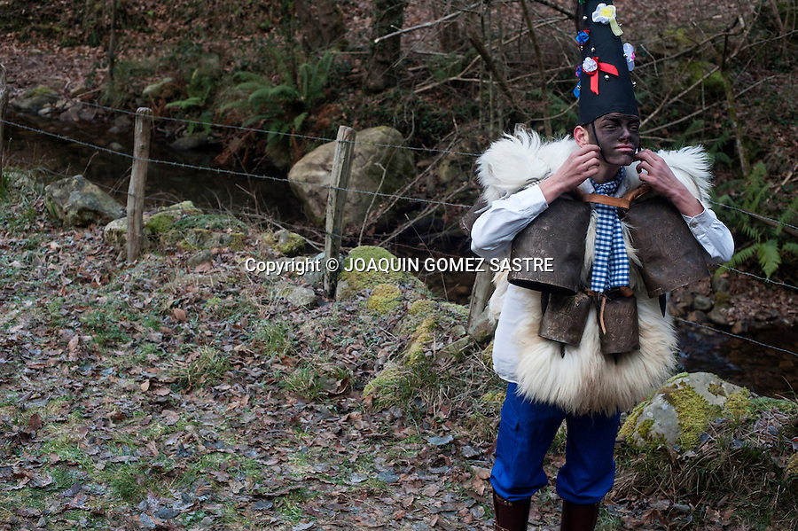 A zarramaco adjusts his hat before starting to participate in the first winter carnival (La Vijanera) in the town cantabra Silio.