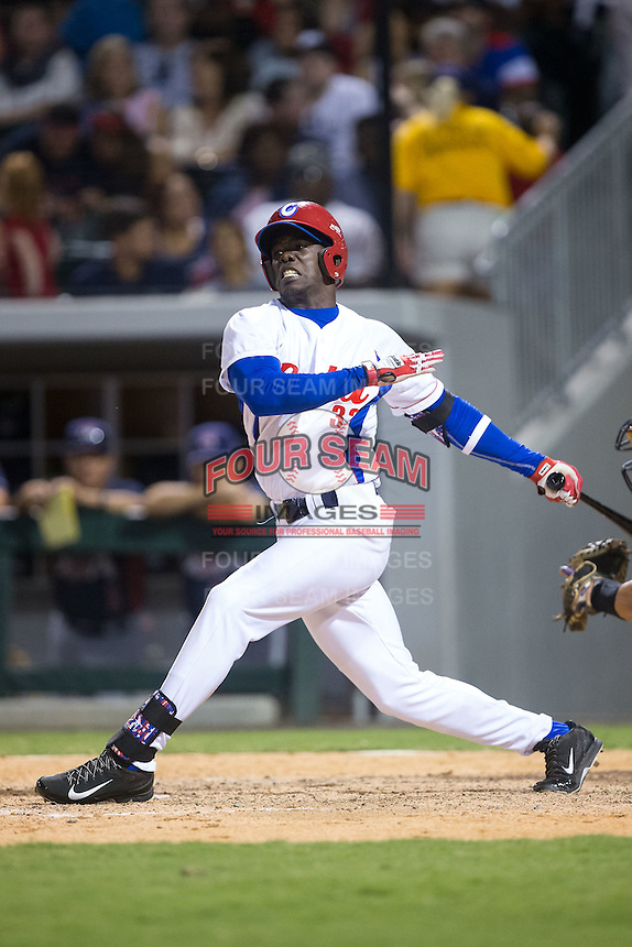 Jose Adolis Garcia Arrieta (32) of the Cuban National Team follows through on his swing against the US Collegiate National Team at BB&T BallPark on July 4, 2015 in Charlotte, North Carolina.  The United State Collegiate National Team defeated the Cuban National Team 11-1.  (Brian Westerholt/Four Seam Images)
