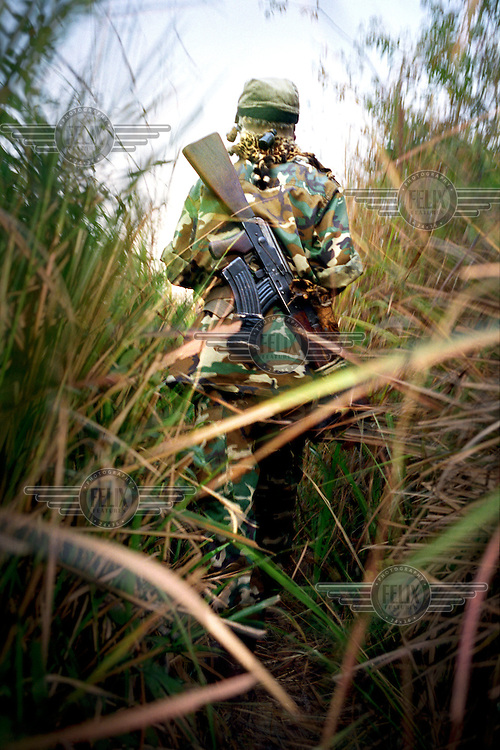 ©Sven Torfinn/Panos Pictures..Eastern Congo, 'Hauts Plateaux' near Uvira, South Kivu,  june 2002..Mai-Mai soldier walking through high grass, bushes, with weapon, carrying machine gun on his back..