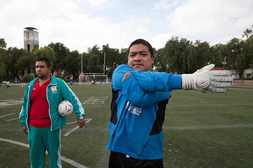 """Rey David Angeles Perez, goalkeeper of Guerreros Aztecas, do warm up before a match against Los Dragones (""""the Dragons"""") in Deportivo Tlalli II in Talnepantla, Mexico on September 27, 2014. Rey, 46, lost his left arm in a work accident in 2012. He is currently unemployed but helps out at his sister's restaurant. Guerreros Aztecas (""""Aztec Warriors"""") is Mexico City's first amputee football team. Founded in July 2013 by five volunteers, they now have 23 players, seven of them have made the national team's shortlist to represent Mexico at this year's Amputee Soccer World Cup in Sinaloa this December. The team trains twice a week for weekend games with other teams. No prostheses are used, so field players missing a lower extremity can only play using crutches. Those missing an upper extremity play as goalkeepers. The teams play six per side with unlimited substitutions. Each half lasts 25 minutes. The causes of the amputations range from accidents to medical interventions – none of which have stopped the Guerreros Aztecas from continuing to play. The players' age, backgrounds and professions cover the full sweep of Mexican society, and they are united by the will to keep their heads held high in a country where discrimination against the disabled remains widespread. (Photo by Bénédicte Desrus)"""