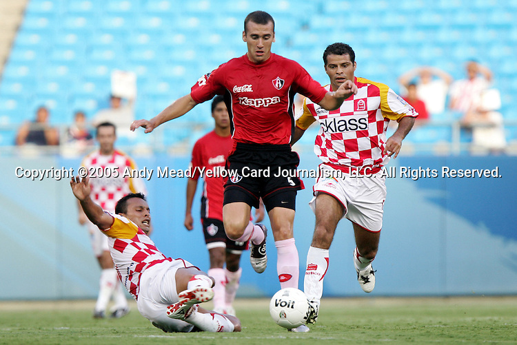 Jose Said Godinez (l) of Tecos tries to slide tackle the ball away from Guillermo Rodriguez (5) of Atlas as Carlos Morales (r) trails the play on Sunday, July 17, 2005, at Bank of America Stadium in Charlotte, North Carolina. U.A.G. Tecos defeated Atlas (both of the Mexican soccer league) in a preseason game.