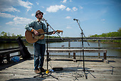 A musician plays on a bridge over the Anacostia river as part of the Kingman Island Bluegrass Festival in Washington, DC.