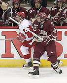 Ben Smith 12 of Boston College and Ben Street 22 of the University of Wisconsin battle in front of the BC bench (Gerbe, Bertram, Rooney). The Boston College Eagles defeated the University of Wisconsin Badgers 3-0 on Friday, October 27, 2006, at the Kohl Center in Madison, Wisconsin in their first meeting since the 2006 Frozen Four Final which Wisconsin won 2-1 to take the national championship.<br />