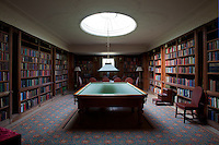 Floor-to-ceiling bookcases clad the walls of the billiard room