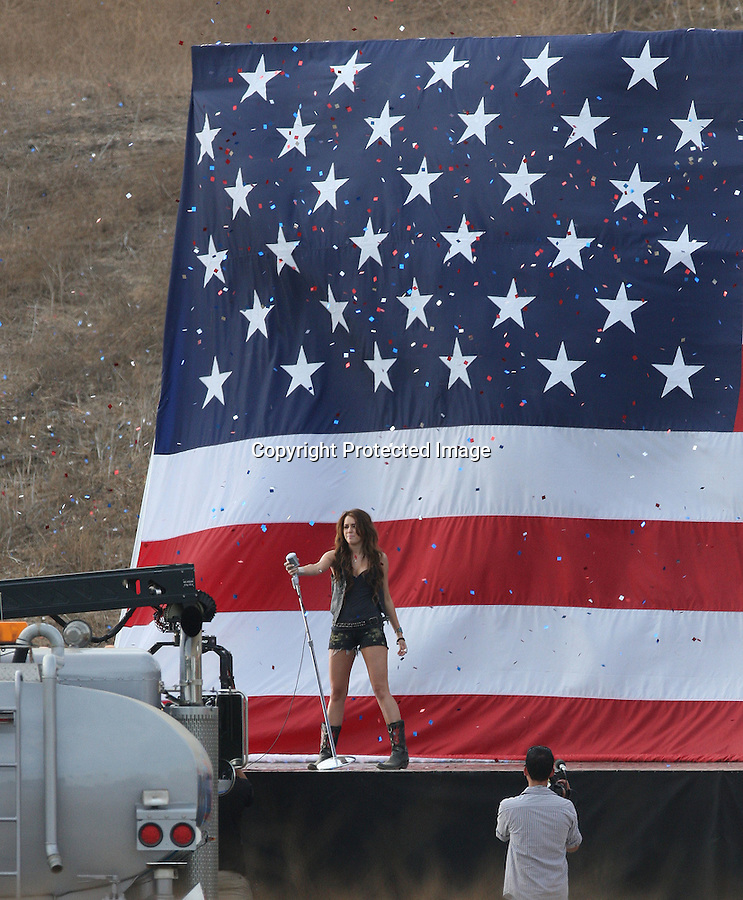 "9-11-09 Friday Exclusive ..Miley Cyrus filming her new music video called ""Party in the U.S.A"" in Los Angeles California. Miley was showing of her Dark blue bra which was exposed during filming.  A gigantic American Flag was set up in the middle of field & confetti was dropped from the sky. Miley was wearing little shorts & cowboy boots.  Miley was also playing on a jungle gym & swings for another scene. ....AbilityFilms@yahoo.com.805-427-3519.www.AbilityFilms.com."