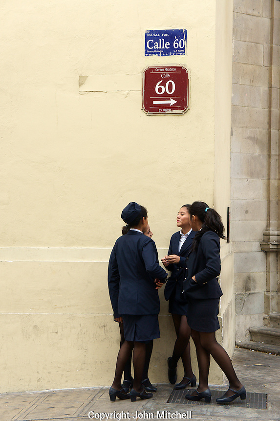 Teenage girls wearing uniforms chatting on a street corner in Merida, Yucatan, Mexico...
