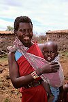 Africa, Kenya, Maasai Mara. A young mother and her baby at Olanana in the Maasai Mara.