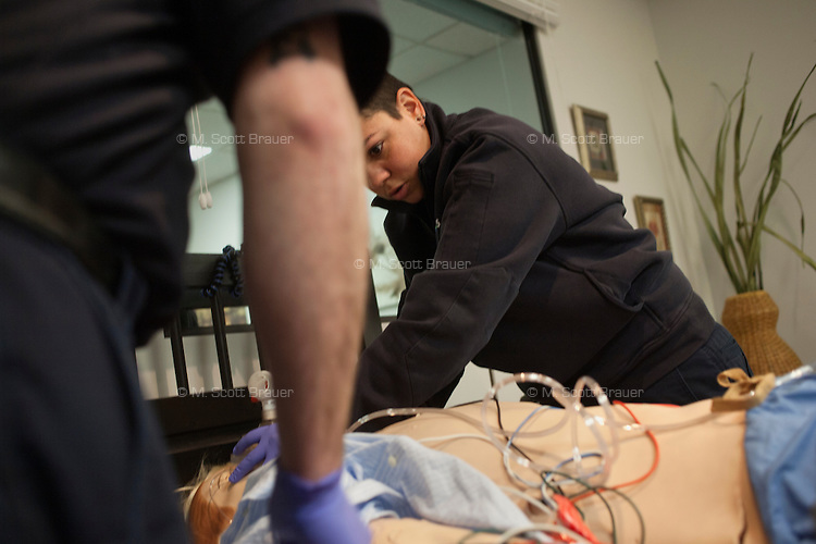 Joel Estes (left) and Melinda Ortega reenact a call in the simulation lab at Pro EMS in Cambridge, Massachusetts, USA.  Using life-like dummies and actual equipment and medicine, the simulation lab allows trainers, students, and working EMTs and paramedics to work on their emergency response technique.   Pro EMS analyzes 100% of their emergency calls, looking at all aspects of the call from travel time to methods used by the EMTs and paramedics.  If this analysis shows ways that the paramedics could have improved their performance on a call, trainers will simulate the conditions of that call, including patient pulse rate and other conditions, in the simulation lab and work with the paramedics to improve their performance.