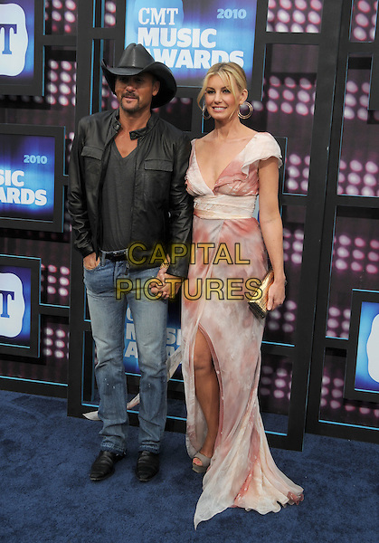 TIM McGRAW & FAITH HILL .2010 CMT Music Awards held at Bridgestone Arena, Nashville, TN, USA, .9th June 2010.country music arrivals full length husband wife couple married jeans cowboy hat grey gray shirt jacket slit split platform sandals pink print dress red long maxi holding hands white cream .CAP/ADM/LF.©Laura Farr/AdMedia/Capital Pictures.