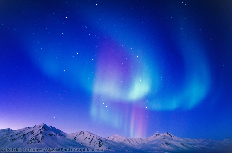 Aurora borealis swirls over the snow covered mountains of the Brooks Range, Arctic National Wildlife Refuge, Arctic, Alaska.