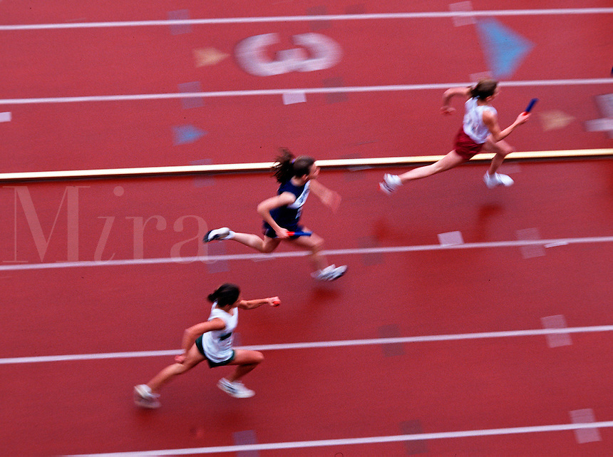 Blurred action overview of female runners at a track meet.