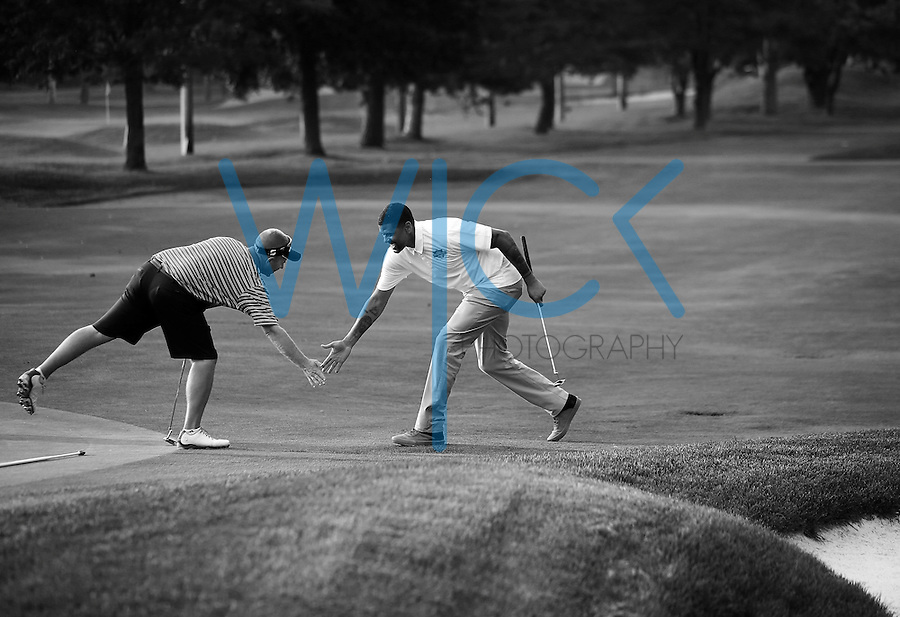 Jalen Rose celebrates with Greg Boll during the 5th annual Jalen Rose Leadership Academy golf tournament at the Detroit Golf Club in Detroit, Michigan on Monday August 31, 2015. (Photo by Jared Wickerham/The Players Tribune)
