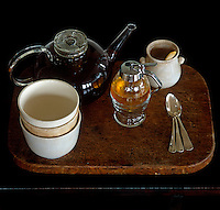 A wooden chopping board serves in place of a tea tray for a mismatched collection of china cups and teapot