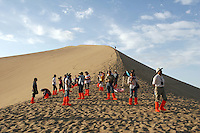 Tourists walking on sand dunes at the tourist attraction of Ming Sha Shan. Dunhuang, Gansu Province. China
