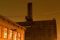 THIS IMAGE IS AVAILABLE EXCLUSIVELY FROM CORBIS<br /> <br /> Please search for image # 42-19897844 on www.corbis.com<br /> <br /> Mysterious Industrial/Factory Scene at night in the Williamsburg, Brooklyn neighborhood of New York City.  The factory building in the background is the the landmarked site of the former Domino Sugar Refinery.....Brooklyn, New York City, New York State, USA