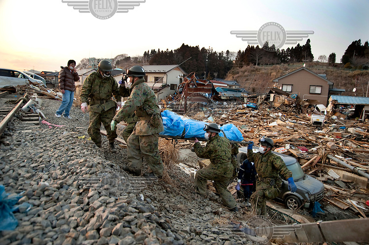 The body of a man who died in the earthquake and Tsunami that struck Northern Honshu is carried up a railway embankment in the destroyed town of Kesennuma by soldiers of the Japan Self Defence Forces (JSDF) after having been recovered from a destroyed house in the town. On 11 March 2011 a magnitude 9 earthquake struck 130 km off the coast of Northern Japan causing a massive Tsunami that swept across the coast of Northern Honshu. The earthquake and tsunami caused extensive damage and loss of life.