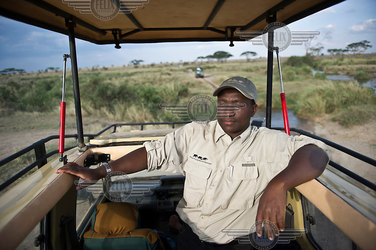 Bernard Kissui, a research scientist for the African Wildlife Foundation, sits in a 4x4 in the Serengeti National Park. The government of Tanzania is planning to turn this dirt track into a highway that will connect isolated communities and bring much needed development to the marginalised Masaai. However, the highway will cut straight through the Serengeti National Park, a World Heritage Site, disrupting animal migration, which would have disastrous consequences for the entire park ecosystem.