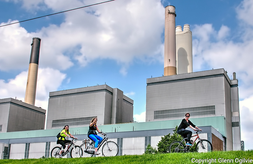 Three unidentified cyclists pass by the Lambton Generating Station, Courtright, Saturday May 27.