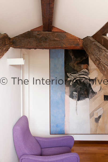 A large painting by Giaquinto and exposed beams with a lilac chair found in a flea market