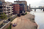 A school fieldtrip group on a beach of the River Thames east of the Millennium bridge, London