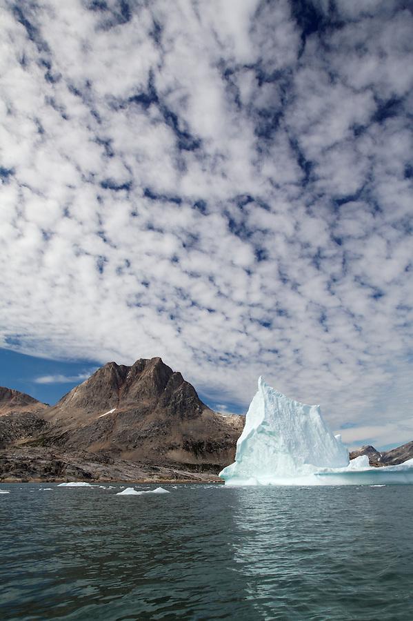 Pinnacled iceberg and mountains, Sammileq Fjord, Ammassalik Island, East Greenland