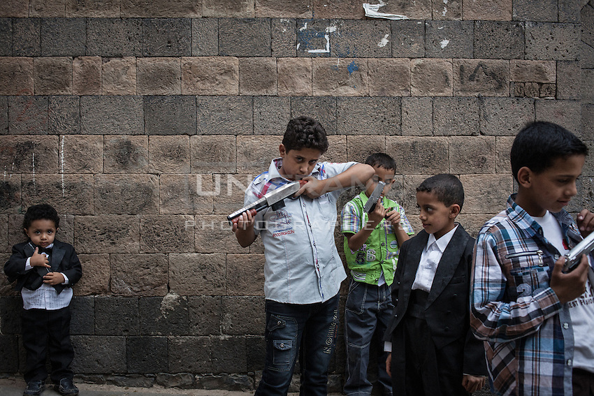 Playful children the first day of Eid holidays dressing new clothes and handling bb guns in Old Sana'a. Yemen is the second most heavily armed society in the World after the United States.