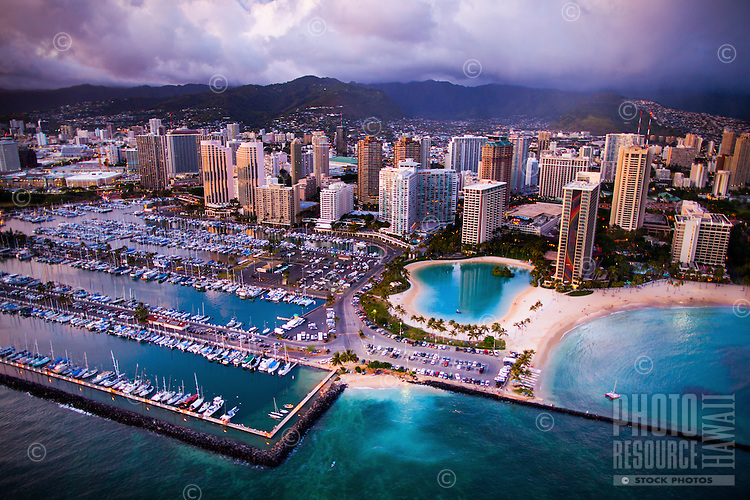 An aerial view at sunset of Ala Wai Harbor, with Waikiki's Hilton Hawaiian Village and the Ilikai hotel in the center and the Ko'olau Range in the far distance, Honolulu, O'ahu.