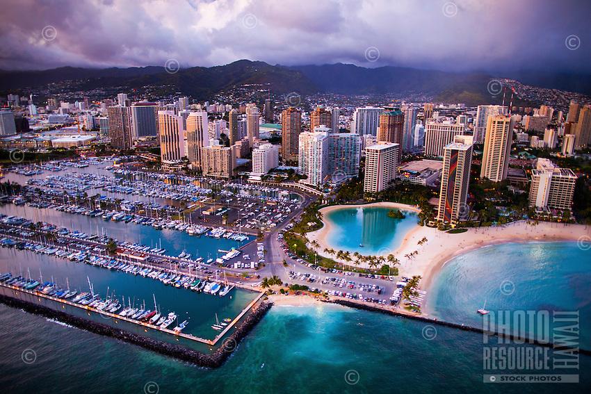 An aerial view at sunset of Ala Wai Harbor, with Waikiki's Hilton Hawaiian Village and the Ilikai hotel in the center and the Ko'olau Range in the far distance, Honolulu, O'ahu.