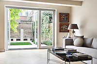 Parquet floors make way for smooth white paving as you walk through the patio doors and into the ultra modern garden