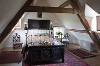 A bedroom situated under the immense A-beam of the house is furnished with a wrought-iron bed, an ancient carved chest and two antique chairs used as bedside tables