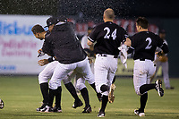 Antonio Rodriguez (left) of the Kannapolis Intimidators is attacked by his teammates after his walk-off hit in the bottom of the 12th innings capped a comeback win over the Hickory Crawdads against the Hickory Crawdads at Kannapolis Intimidators Stadium on April 22, 2017 in Kannapolis, North Carolina.  The Intimidators defeated the Crawdads 10-9 in 12 innings.  (Brian Westerholt/Four Seam Images)