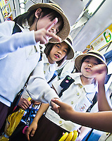 "Tokyo school children head home on the train seen here playing a game of ""scissors-paper-rock""."