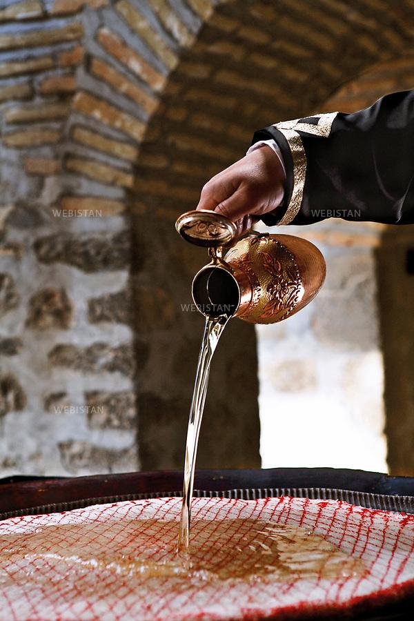 Azerbaijan, Sheki (Shaki), Karavan Saray Hotel, March 30, 2012<br /> Men make Sheki halva, a gooey candied baklava that is often referred to as the Sheki sweet. A net is made of fried dough and sugar, and when it hardens, <br /> it is spread with a hazelnut paste and covered with honey.<br /> <br /> Azerba&iuml;djan, Cheki (Shaki), h&ocirc;tel Karavan Saray, 30 mars 2012. <br /> Les hommes font du halva de Cheki, un baklava confit souvent consid&eacute;r&eacute; comme la p&acirc;tisserie de la r&eacute;gion. On pr&eacute;pare une couche de sucre et de p&acirc;te frite, qu&rsquo;on laisse durcir. Une p&acirc;te de noisette est ensuite appliqu&eacute;e sur le dessus, puis recouverte avec du miel.