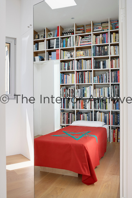 A view through an open mirrored door to a single bed with built in bookshelves behind