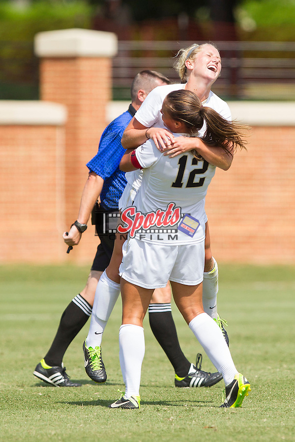 Riley Ridgik (2) of the Wake Forest Demon Deacons gets a hug from teammate Katie Stengel (12) after scoring a goal against the Miami Hurricanes at Spry Soccer Stadium on September 15, 2013 in Winston-Salem, North Carolina.  The Deacons defeated the Hurricanes 4-0.   (Brian Westerholt/Sports On Film)
