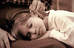 Sepia-toned image of cute little girl sleeping in the safety of her grandmother's lap