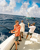 USA, Florida, three men fishing on the back of a boat, Islamorada