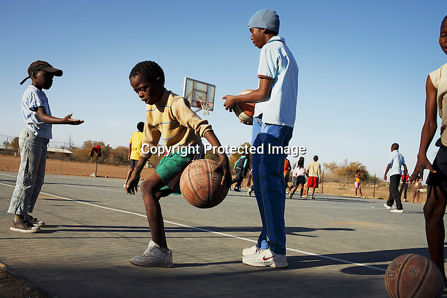 Youth train basketball on a court in Gaborone, Botswana. They are benefiting from ACHAP, African Comprehensive HIV/Aids Partnerships, collaboration between the Government of Botswana, the Bill & Melinda Gates foundation and Merck to prevent and treat HIV/Aids in Botswana. NBA players came to Botswana to give a fitness and basketball clinic at the newly opened court. .Photo by: Per-Anders Pettersson/Getty Images For TIME Magazine.