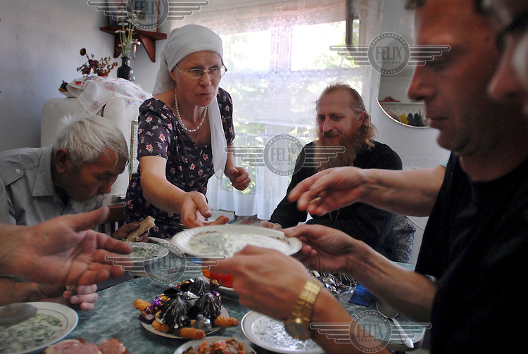Father Alexander (right centre) has a meal with members of his Russian Orthodox congregation.
