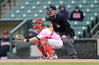 Rochester Red Wings catcher Chris Herrmann #18 and umpire Toby Basner during a game against the Columbus Clippers on May 12, 2013 at Frontier Field in Rochester, New York.  Rochester defeated Columbus 5-4 wearing special pink jerseys for Mother's Day.  (Mike Janes/Four Seam Images)