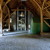 The structure of the old beams of the vaulted ceiling of the barn contrast with the modern facade of the house