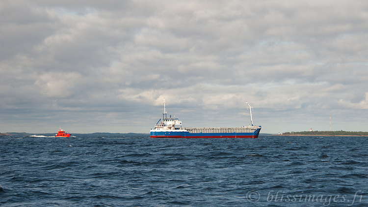 Pilot boat chases ship passing Orrengrund lighthouse in southern Finland.