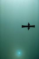 Man paddlling canoe in fog