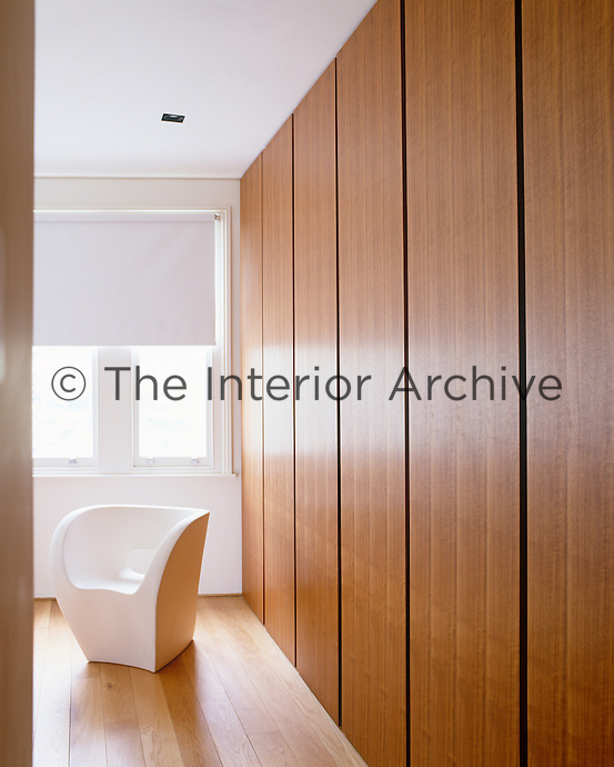A bespoke wardrobe covers an entire wall of this contemporary bedroom