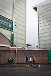 Home fans making their way past the Famous Five Stand at Easter Road stadium before the Scottish Championship match between Hibernian and visitors Alloa Athletic. The home team won the game by 3-0, watched by a crowd of 7,774. It was the Edinburgh club's second season in the second tier of Scottish football following their relegation from the Premiership in 2013-14.